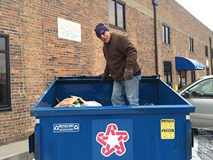A Volunteer Standing in the Dumpster